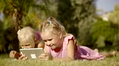 flatbed : two little blonde girls are smiling and laughing, lying on grass in a yard in day and using a tablet