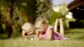 flatbed : two little sisters are lying on a grass in a garden in summer day and watching video on a tablet