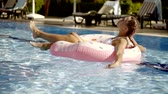 sunburn : A young woman is bathing in the pool on an inflatable lap, the lady is relaxing in the water and enjoying the summer holidays