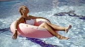 bronzeado : A young woman bathes in a pool on an inflatable circle that looks like a donut, a lady spends time in the water Vídeos