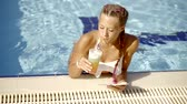 kurum : Young women who are in a swimming pool holding a tablet and a tasty fruit juice, the lady looks at the monitor Stok Video