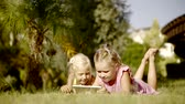 karikatury : Two funny girls lie on the grass in a warm sunny day, the sisters are holding a tablet in order to watch cartoons