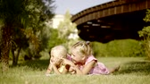 karikatury : Little girls lie on the grass in the park, sisters chatting with each other on a sunny summer day