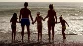 klapki : A friendly family stands near the waves on the beach, they hold hands and resist the waves during the holidays