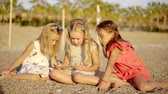 sideview : Adorable little girls are enjoying the game on a beach. Stock Footage