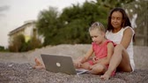sideview : Family sits on the beach with laptop in the evening. Stock Footage