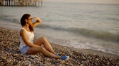 sideview : Beautiful woman watches sunset on the beach