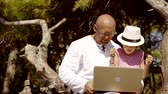 sideview : Father and daughter is sitting on the branch with a laptop