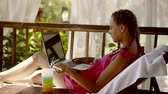 sideview : Attractive woman lies in launger with a laptop