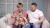 окно : young family and their newborn daughter home on the couch. bright and festive interior Стоковые видеозаписи