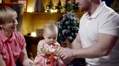 ваш : cute couple in festive interior swing your baby on the rocking horse and gently kiss each other