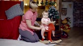 nevetés : mother playing with baby girl in the rocking horse. childrens room with a festive interior
