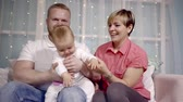 yanak : successful young family at home in the holiday interior with a baby daughter on the knee of a parent. mom with short hair Stok Video