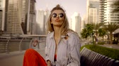 refletindo : cheerful relaxed blonde is sitting on a bench and dancing, skyscrapers are reflecting in sunglasses