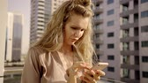 enviar : rich adult woman is standing on a terrace of her apartment in a big modern city, looking on a smartphone