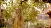 удивительно : tender blonde woman is walking in a blooming garden under large trees in sunny day, touching hair Стоковые видеозаписи