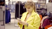 продавщица : Lovely woman in a boutique with a smartphone