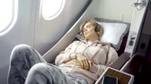 espaçoso : tired dreamy girl is in a bed in first class airplane, earphones are on her head, she is turning and stretching