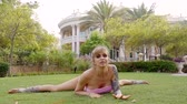протяжение : sensual flexible woman is sitting on a lawn with legs spread in sides and stretching her muscles, front view