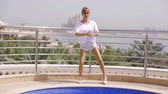 quadril : slim young woman is doing squats outdoors near swimming pool in courtyard of home in sunny day