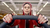 náhradník : The girl athlete in a red jacket is engaged in cardio training in a sports club. Listens to your favorite music with large headphones. Dostupné videozáznamy