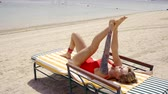 укрепление : Shot of a charming woman stretching on the beach.