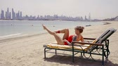 укрепление : Attractive blonde woman is lying on the lounge on the beach and doing bicycle crunches.