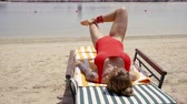 şezlong : sportswoman is training in a beach, lying face up on a deck chair and straining the muscles of belly and legs Stok Video