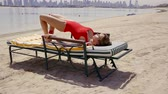 one joint : gymnast woman is doing workout on a vacation, lying on a sunbed on a sea coastline and lifting thighs