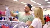 advise : cute married pair of sporty man and blonde woman are looking on clothes for their little daughter in a store, smiling