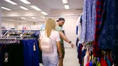 kanca : man and woman are walking over trading area in clothing store and consulting with each other Stok Video