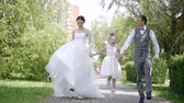 compromisso : Model released bride and groom walk in the Park with the little girl sisters hands in love on the wedding day