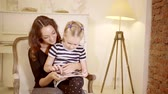 flatbed : little girl is sitting on knees of her young mother and playing a tablet Stock Footage