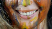 vislumbre : close-up view of face of young woman, painted by multicolor dyes, smiling and looking to a camera Vídeos