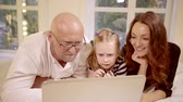 daugther : Family lying in bed using a laptop