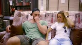 fermuar : A couple in love is considering a new purchase, they are sitting on the couch and holding pillows Stok Video