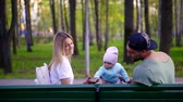 recém nascido : young family sitting on bench in park, husband and his wife playing with little child Stock Footage