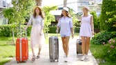 roll on bag : three slender tourist girls roll suitcases on the well-groomed territory of the hotel at the resort