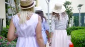 roll on bag : three slender tourist girls roll suitcases on the well-groomed territory of the hotel at the resort. straw hats on the heads Stock Footage