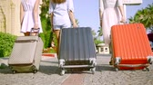 roll on bag : close up. three slim girls tourist wheeled suitcases across the stone road. shooting from below Stock Footage
