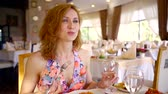 white wine dish : pretty woman with red hair is dining at a table with her man in a restaurant talking and eating a gourmet dish writing down an expensive white wine