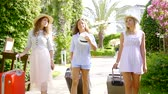 elegáns : group of three girls head to their hotel in a tropical Park. women tourists with suitcases on vacation