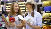 womens : two cute girlfriends choose a pair of shoes and have fun in the store