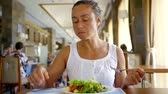 lunchroom : a young woman eats a green salad, a lady gently holds a fork and knife