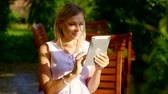 impressão : young woman reading a book on a portable tablet, she smiles and sits on a bench Stock Footage