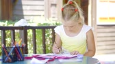 atento : funny and calm girl is engaged in drawing paints at the desk on the veranda