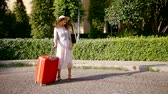 outro : alone woman with luggage is waiting her two friends women in sunny street, meeting and hugging each other