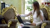 продавщица : young businesswoman is taking notebook, open it and starting to work, sitting in a luxury armchair