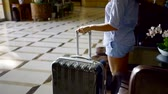 carry out : brunette girl is wearing straw hat, shorts and shirt is rising from a couch in a vestibule, taking her suitcase and going out Stock Footage