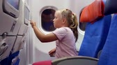 cabine : little child girl is passenger of airplane, is sitting on a seat in cabin, looking on a display in chair